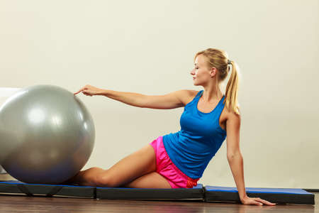 Foto für Sport, training, gym and lifestyle concept. Young attractive slim woman in sportswear doing fitness exercises with fit ball at home - Lizenzfreies Bild