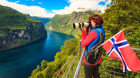 Photo pour Tourism holidays picture and traveling. Woman tourist enjoying fjord landscape Geirangerfjord from Ornesvingen eagle road viewpoint, taking photo with camera, Norway. - image libre de droit