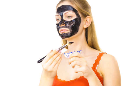 Photo pour Woman applying with brush black detox mud mask to her face. Girl taking care of skin. Spa treatment. Skincare. - image libre de droit
