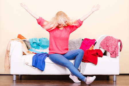 Photo pour Clothing dilemmas concept. Blonde woman with windblown does not know what to wear sitting on messy couch with piles of clothes. - image libre de droit