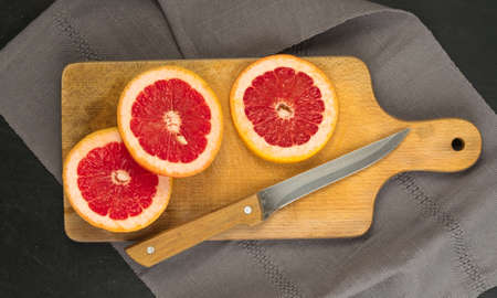 Red Grapefruit with Orange Peel Closeup. Sections of Juicy Bittersweet Fruit. Sliced Ruby Citrus