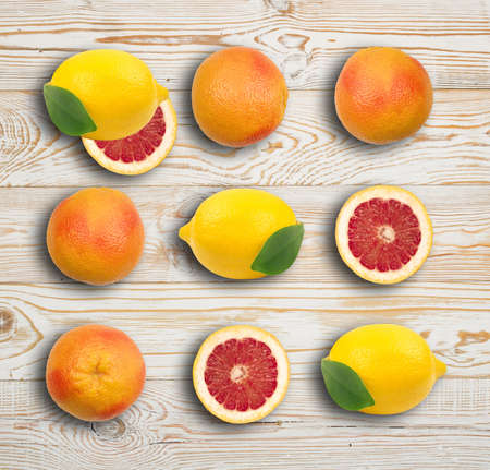 Whole Red Grapefruit with Orange Peel on Wooden Background Closeup. Section of Juicy Bittersweet Fruit. Ruby Citrus and Lemon Pattern