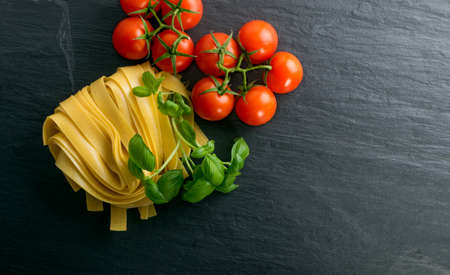 Photo for Raw yellow italian pasta pappardelle, fettuccine or tagliatelle close up. Egg homemade dry ribbon noodles, long rolled macaroni or uncooked spaghetti with tomatoes and basil top view - Royalty Free Image