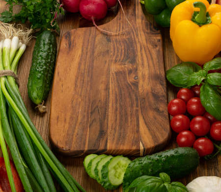 Foto für Cutting board vegetables mockup. Chopping board with fresh cucumbers, greens, peppers and cherry tomatoes ready for salad with copy space - Lizenzfreies Bild