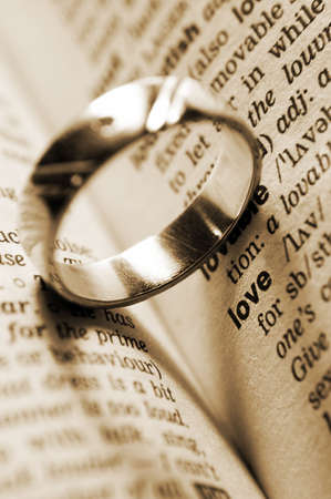 wedding ring near dictionary entry word love in sepia