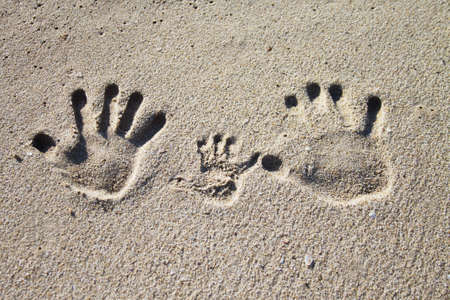 Three palm imprints of family on sand