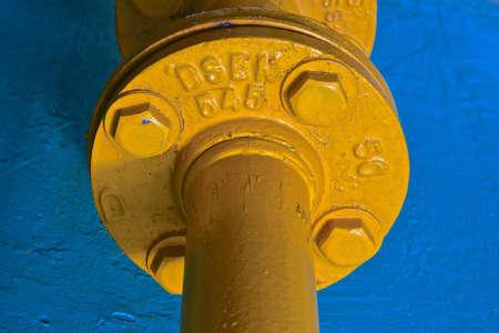 Photo pour A close up view of a large yellow industrial pipe against a blue stone background.  - image libre de droit