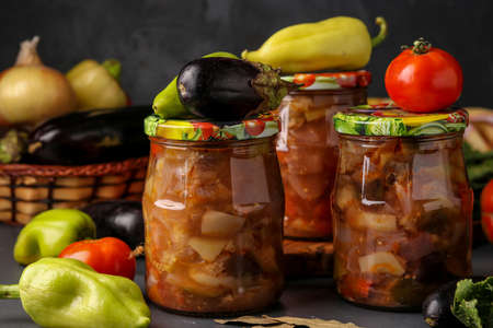 Photo pour Vegetable salad with eggplant, onions, peppers and tomatoes in jars on a dark background, horizontal orientation, close up - image libre de droit