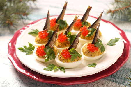 Photo pour Eggs stuffed with sprats and red caviar on a white plate. Festive snack - image libre de droit