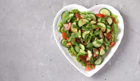 Photo pour Heart-shaped plate with healthy salad with tomatoes, cucumbers, arugula and microgreens on gray concrete background, Space for text - image libre de droit