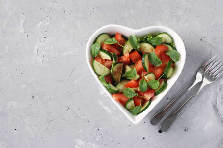 Photo pour Heart-shaped bowl with salad of tomatoes, cucumbers, arugula and radish microgreens on gray concrete background, healthy eating day, space for text - image libre de droit
