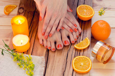 SPA. Skin care of a beauty female hands and feet with candles, oranges, cream and flowers