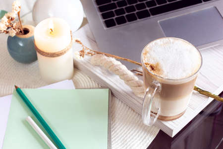 the laptop with coffee and notebook with pencils on a table