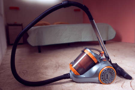 vacuum cleaner with orange color on a bedroom background