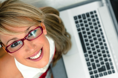 overhead shot of an attractive young female with glasses in front of a laptop