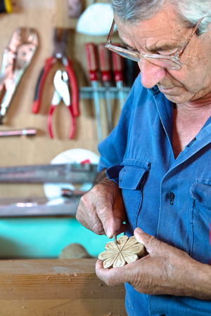 hands of craftsman in workshop manually sanding on workbench a decorative figura of wood with carpenters tool in hands / cabinetmaker modeling a decorative piece of wood