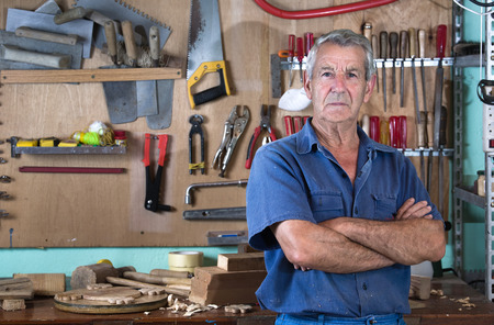 Photo pour Portrait of a worker in work clothes in front of workbench tools / Portrait of man at work in workshop in garage at home - image libre de droit