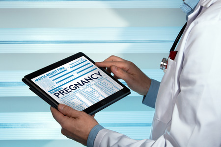 doctor with medical record digital on the tablet with text pregnancy in diagnostic / gynecologist holding Tablet with pregnancy diagnosis in digital medical reportの写真素材