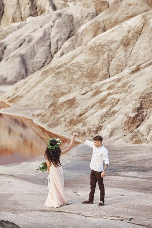 Bride and groom walk along the red mountains, fabulous scene. Couple in love holding hands. Fall wedding outdoors
