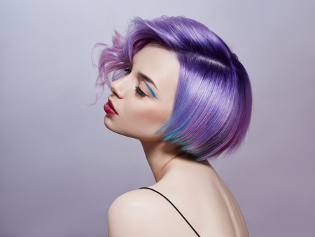 Photo pour Portrait of a woman with bright colored flying hair, all shades of purple. Hair coloring, beautiful lips and makeup. Hair fluttering in the wind. Sexy girl with short  hair. Professional coloring - image libre de droit