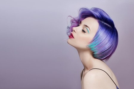 Foto de Portrait of a woman with bright colored flying hair, all shades of purple. Hair coloring, beautiful lips and makeup. Hair fluttering in the wind. Sexy girl with short  hair. Professional coloring - Imagen libre de derechos