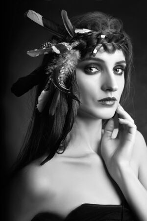 Photo pour Indian woman with feathers in her hair, portrait of American Indian girl beauty on dark background in smoke. Beautiful face with clean skin, contrast makeup - image libre de droit