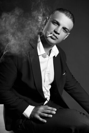 Photo for Contrast portrait of a Smoking man businessman in an expensive business suit on a dark background. Successful emotional Manager businessman posing gestures hands and Smoking cigarette on a black - Royalty Free Image