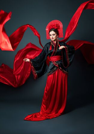 Photo pour Woman is dressed in red Chinese Japanese folk clothing. Flying fabric, beautiful umbrella and fan in Japanese Chinese style, long earrings in the ears. Girl posing on a dark background - image libre de droit