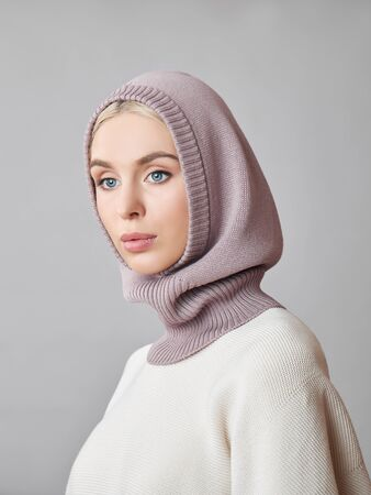 Photo pour European Muslim woman with a blonde hair in a bonnet hood dressed on her head. Beautiful girl in sweater with soft skin, natural cosmetics - image libre de droit
