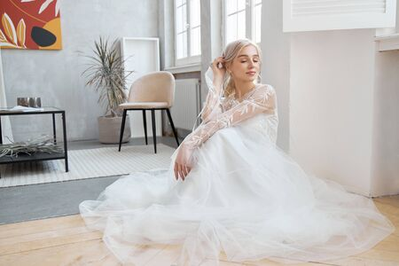 Photo pour Ideal bride sitting on the floor, portrait of a girl in a long white dress. Beautiful hair and clean, soft skin. Wedding hairstyle blonde - image libre de droit