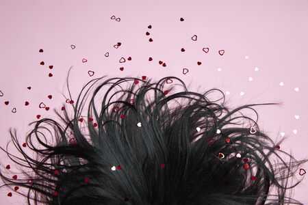Foto de Black Hair on a pink background. Beautiful and strong hair, hair texture, root care - Imagen libre de derechos