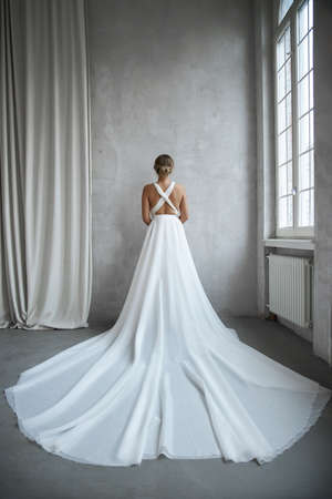 Photo pour Beautiful slender woman in white wedding dress, new collection of dresses for the bride. Noise, out of focus - image libre de droit