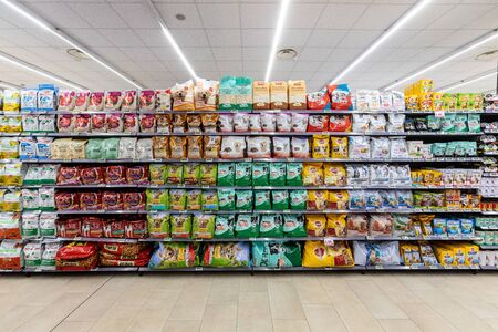 Foto de Rome / Italy. December 05, 2018: Shelving with products of different nature, variety of food displayed on the shelves inside a MA supermarket in Rome in Italy. Pet food. - Imagen libre de derechos