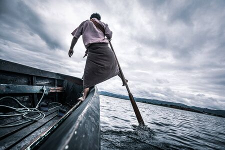 Photo pour Local fishermen practicing a distinctive rowing style which involves standing at the stern on one leg and wrapping the other leg around the oar. - image libre de droit