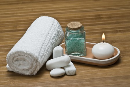 Spa background with bath salts and a candle.
