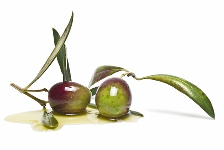 Two green olives on some olive oil isolated on a white background.