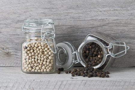 Black and white peppercorns on an old wooden surface.
