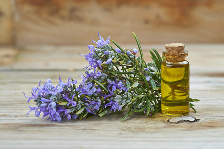 Rosemary essential oil in a small glass vial and plant with flowers on a wooden