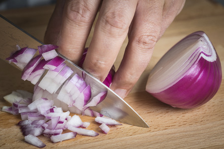 Chef choppig a red onion with a knife on the cutting board