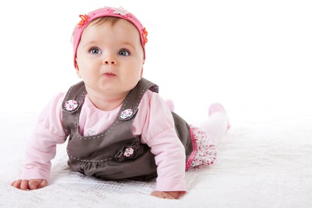 Photo for A baby girl is crawling along the floor with an inquisitive look on her face.  Horizontal shot. - Royalty Free Image