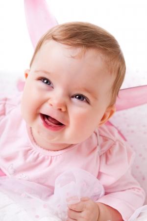 Foto de A cute baby girl in fairy wings laughs while looking up at the camera.  Vertical shot. - Imagen libre de derechos