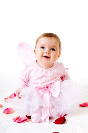 Photo for A cute baby girl dressed in a fairy costume sits amongst flower petals and smiles upwards.  Vertical shot. - Royalty Free Image