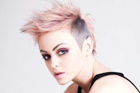 Head and shoulders portrait of an attractive young woman with wild pink hair. Horizontal shot.