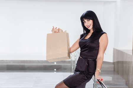 Foto de Young Pretty smiling brunette woman dressed in a black business suit holding paper shopping bag, walking on a mall. Looking at camera. - Imagen libre de derechos