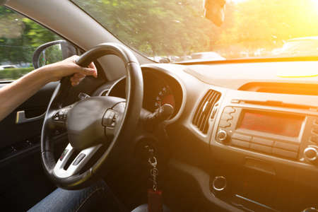 Foto de A woman drives a car with one hand. Woman hand holding a steering wheel confidently. Hand on wheel woman driving car - Imagen libre de derechos