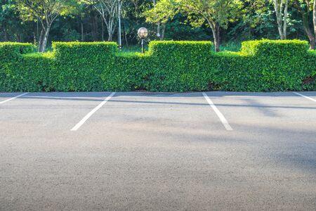 Foto de Empty space of car parking lot with green bush in the background. - Imagen libre de derechos