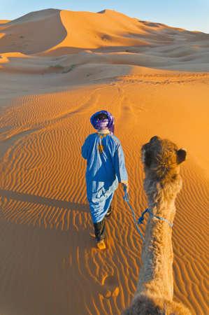 Berber walking with camel at Erg Chebbi orange dunes, Morocco