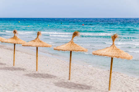 Straw umbrellas on sand beach and clear sky.