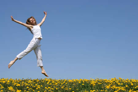 Smiling pretty girl in summer white clothes dancing in a flowering meadow.