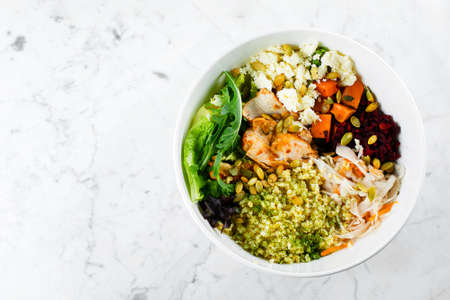 Photo pour Top view of healthy pumpkin seasonal bowl. Salad with meat, cheese, bulgur and vegetables on marble background. Copy space - image libre de droit